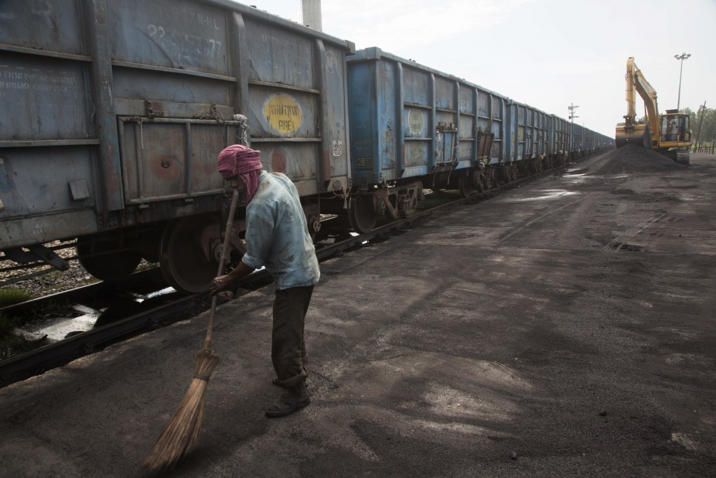 In this July 14, 2017 photo, Baburam sweeps domestically produced petroleum coke to be transported onto trucks hired by local factories in Rampur abou...