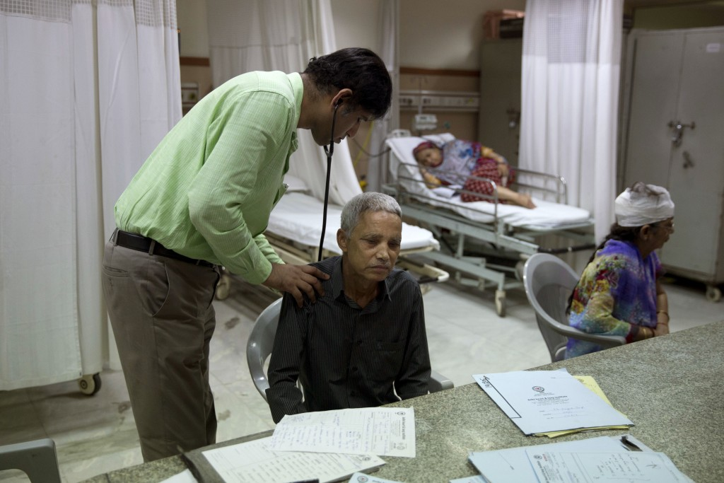 In this Oct. 23, 2017 photo, a doctor examines Jagat Singh, 59, at the Delhi Heart and Lung Institute in New Delhi, India. Over the past decade, pollu...
