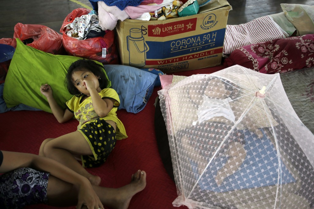 In this Saturday, Dec. 2, 2017, file photo, a girl rests next to her brother in a temporary shelter following the eruption of Mount Agung in Klungkung