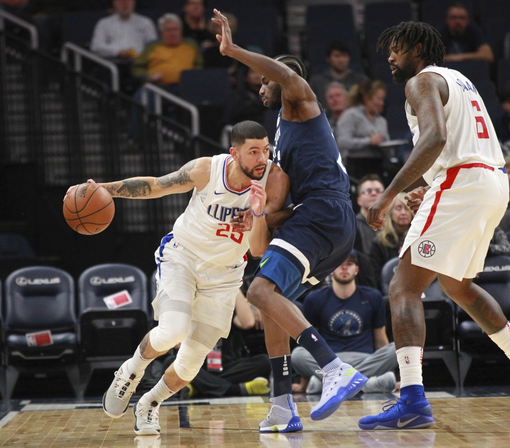 Los Angeles Clippers guard Austin Rivers (25) drives on Minnesota Timberwolves guard Andrew Wiggins (22) with Los Angeles Clippers forward DeAndre Jor...