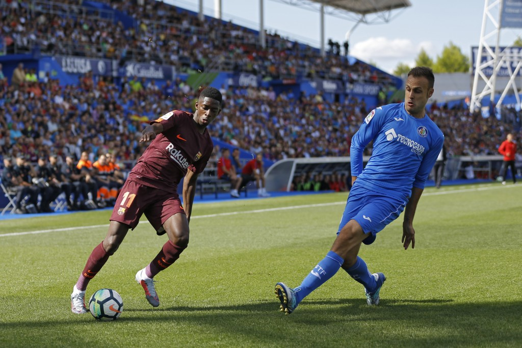 """FILE - In this Sept. 16, 2017 file photo, Barcelona's Ousmane Dembele, left, duels with Getafe's Juan Torres Ruiz """"Cala"""" before getting injured during"""