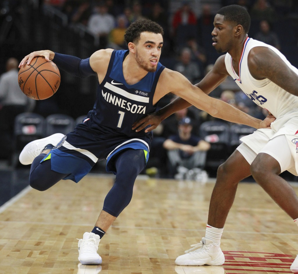 Minnesota Timberwolves guard Tyus Jones (1) drives around Los Angeles Clippers guard Jawun Evans (1) in the first quarter of an NBA basketball game on...