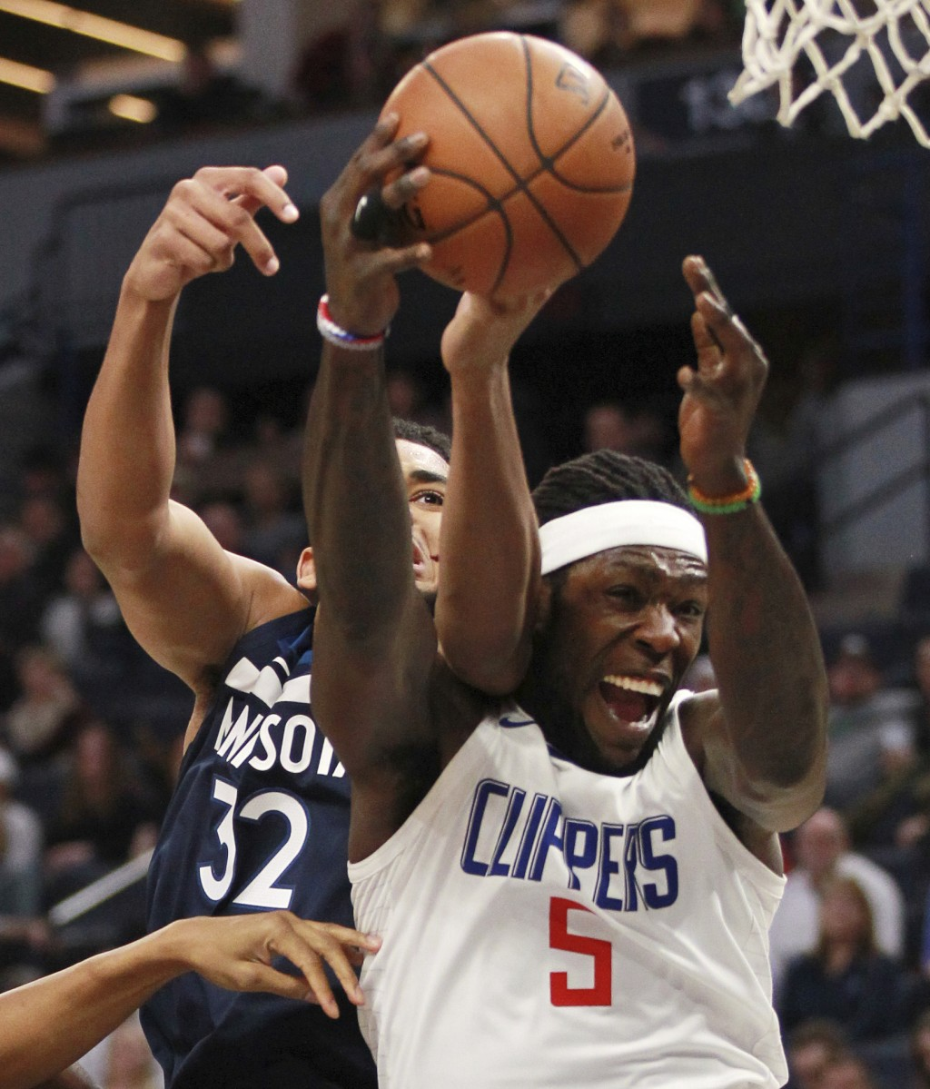 Minnesota Timberwolves forward Karl-Anthony Towns fights for a rebound with Los Angeles Clippers Montrezl Harrell (5) in the second quarter of an NBA ...