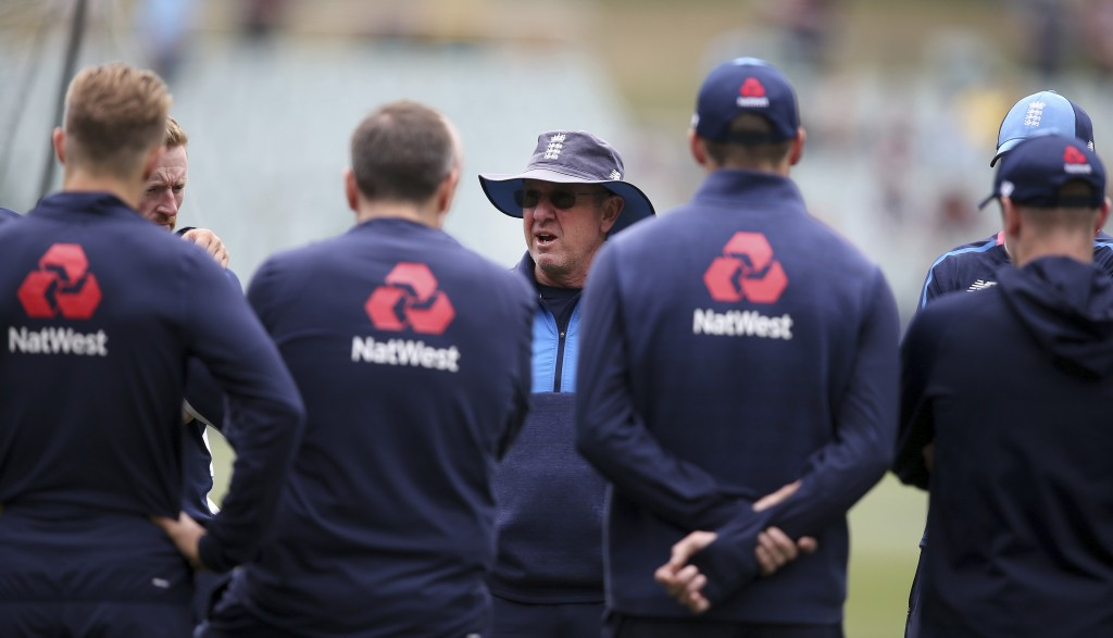 England's head coach Trevor Bayliss talks with his players before the start of the third day of their Ashes cricket test match in Adelaide, Monday, De