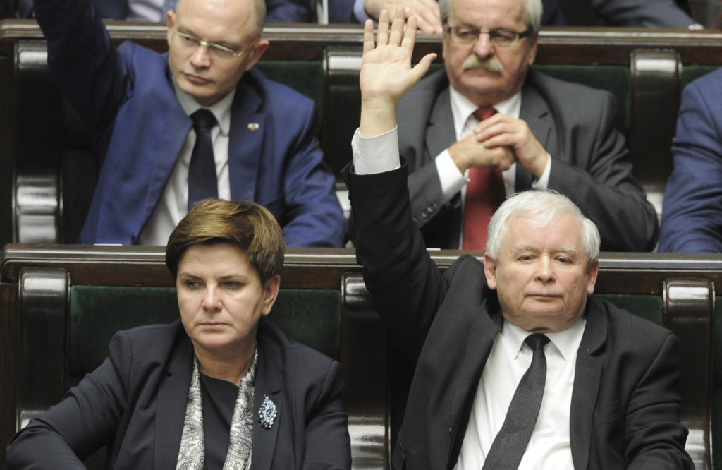 FILE - In this Dec. 22, 2015 file photo the leader of the ruling Law and Justice party, Jaroslaw Kaczynski, right, raises his hand during one of the v
