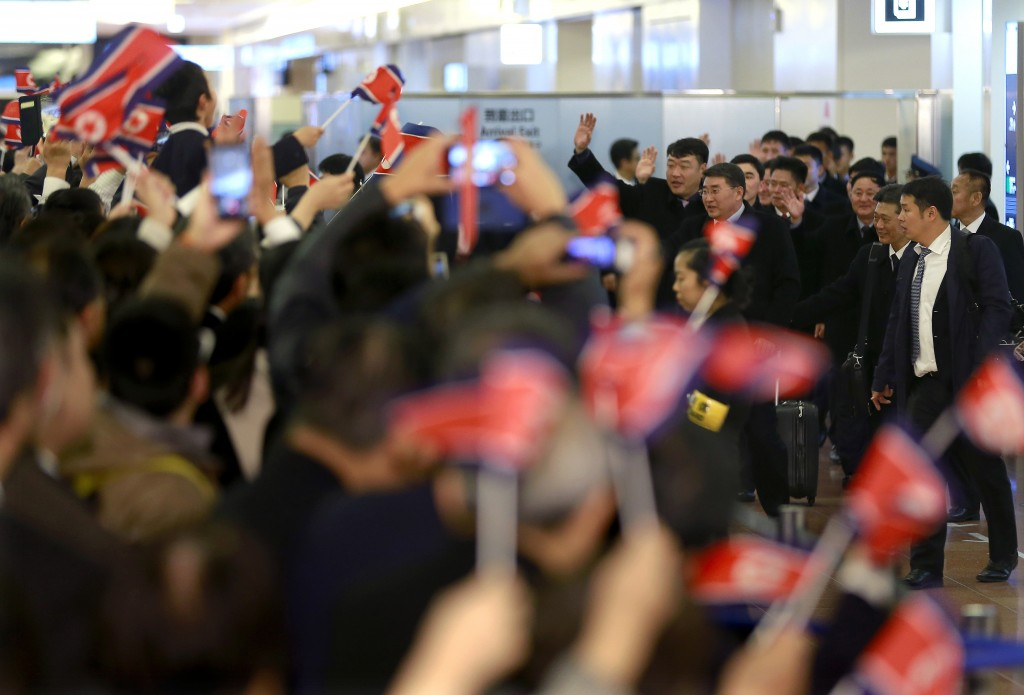 North Korean men's national soccer team members are welcomed with their national flags waved upon arrival at Haneda international airport in Tokyo Tue