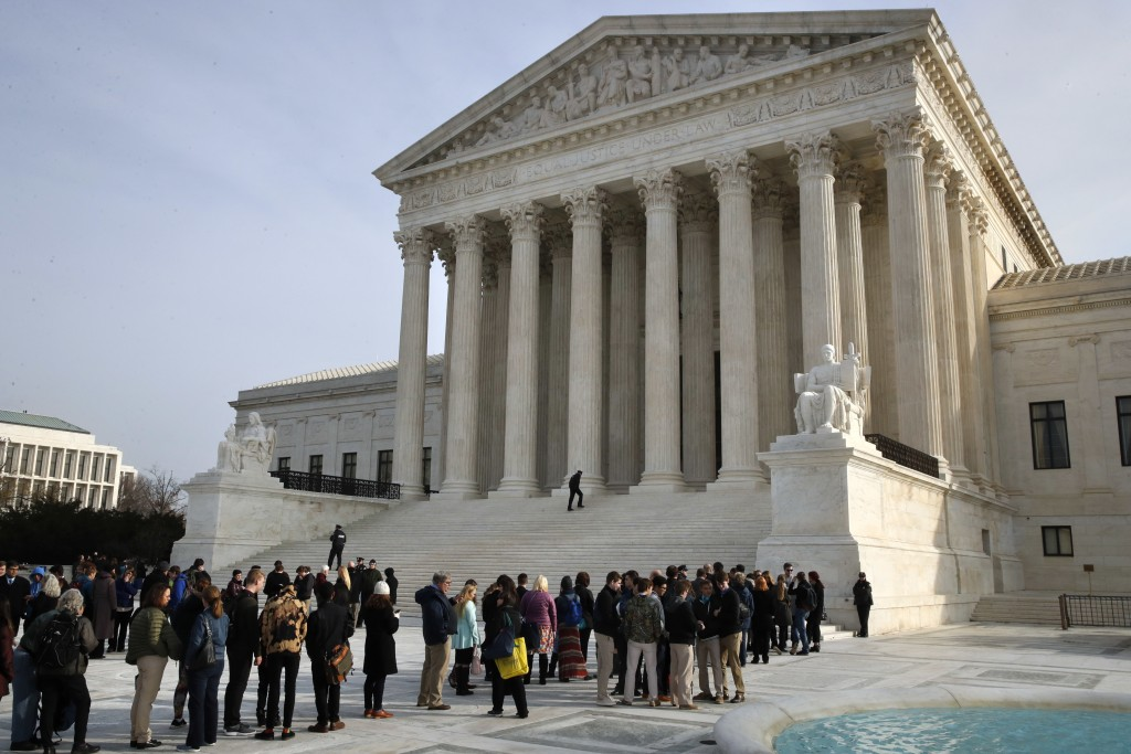 People stand in line to enter the Supreme Court where a case on sports betting is being heard, Monday, Dec. 4, 2017, in Washington. (AP Photo/Jacquely
