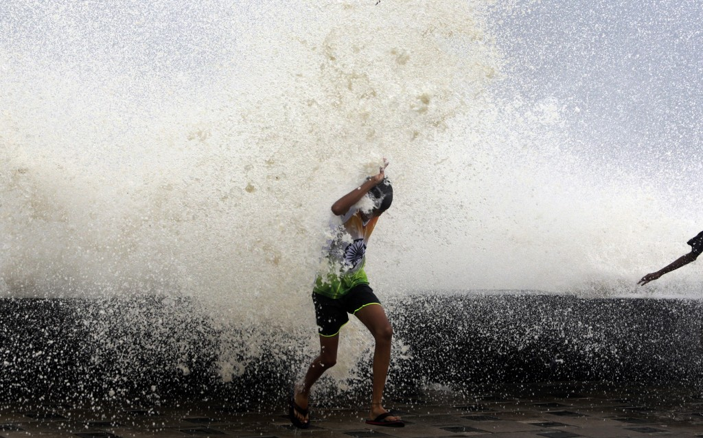 In this Tuesday, Dec. 5, 2017, file photo, an Indian boy is drenched by waves during high tide in the Arabian Sea in Mumbai, India. A rain and thunder
