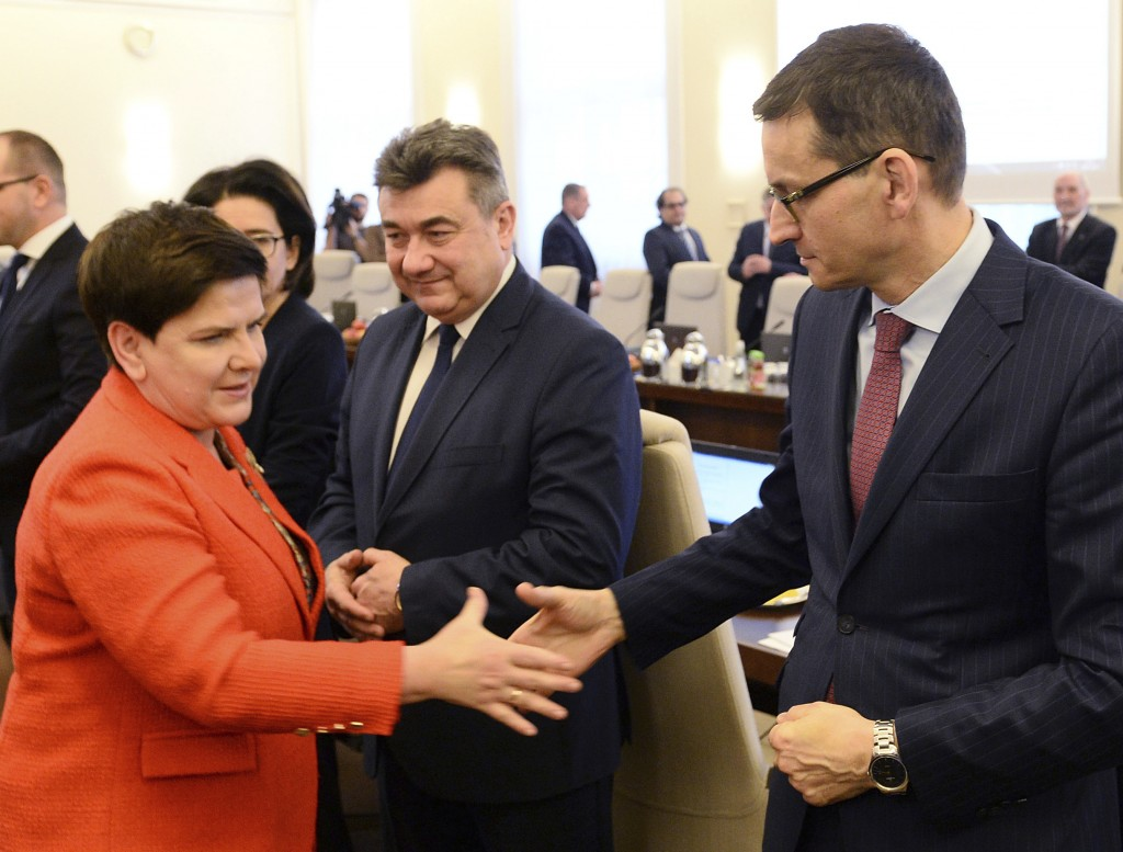 Poland's Prime Minister Beata Szydlo, left, shakes hands with Finance Minister Mateusz Morawiecki, right, prior to a government meeting in Warsaw, Pol