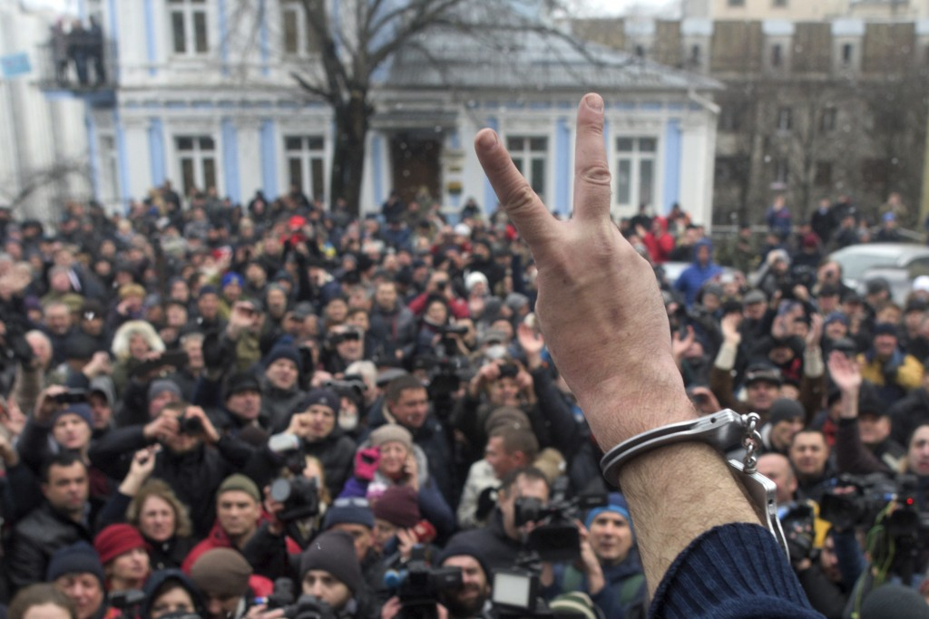 Former Georgian president Mikheil Saakashvili, back to a camera, gestures to protesters after he escaped with help from supporters and led them on a m
