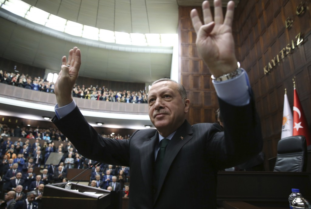 Turkey's President Recep Tayyip Erdogan waves as he arrives to deliver a speech during a meeting of his ruling Justice and Development Party (AKP), in