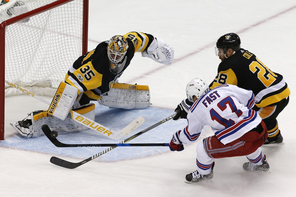 Pittsburgh Penguins goalie Tristan Jarry (35) blocks a shot by New York Rangers' Jesper Fast (17) with Ian Cole (28) defending during the third period