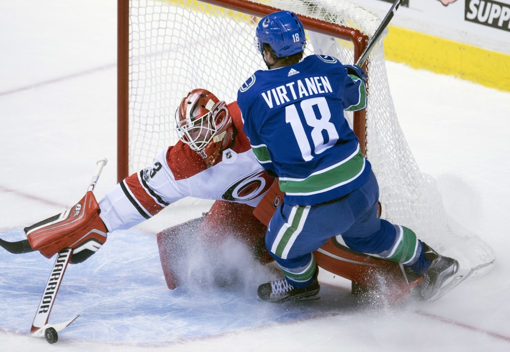 Vancouver Canucks right wing Jake Virtanen (18) tries to get a shot past Carolina Hurricanes goalie Scott Darling (33) during the second period of an
