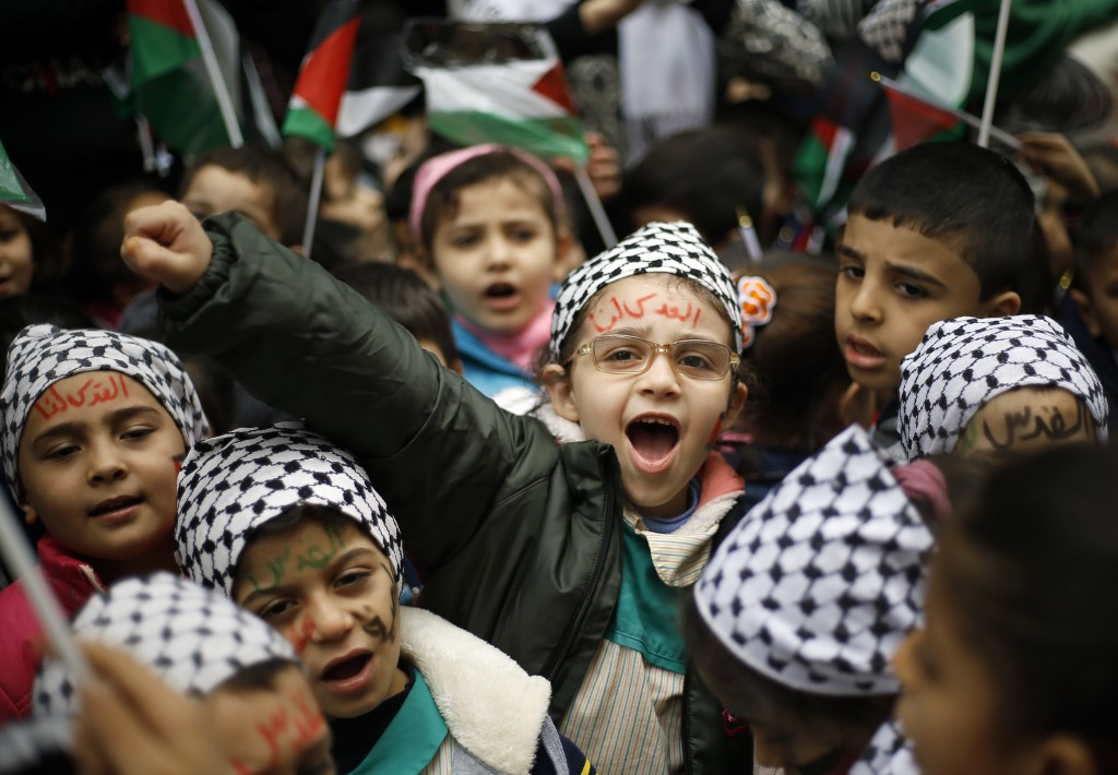 """A girl with Arabic painted on her face that reads, """"Jerusalem is for us,"""" chants slogans during a sit-in in the Bourj al-Barajneh Palestinian refugee"""