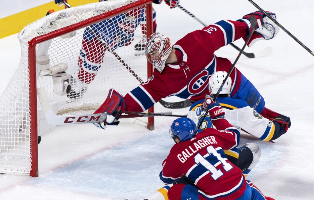 The puck goes into the net past Montreal Canadiens goalie Carey Price on a goal by St. Louis Blues' Scottie Upshall (9) during the second period of an
