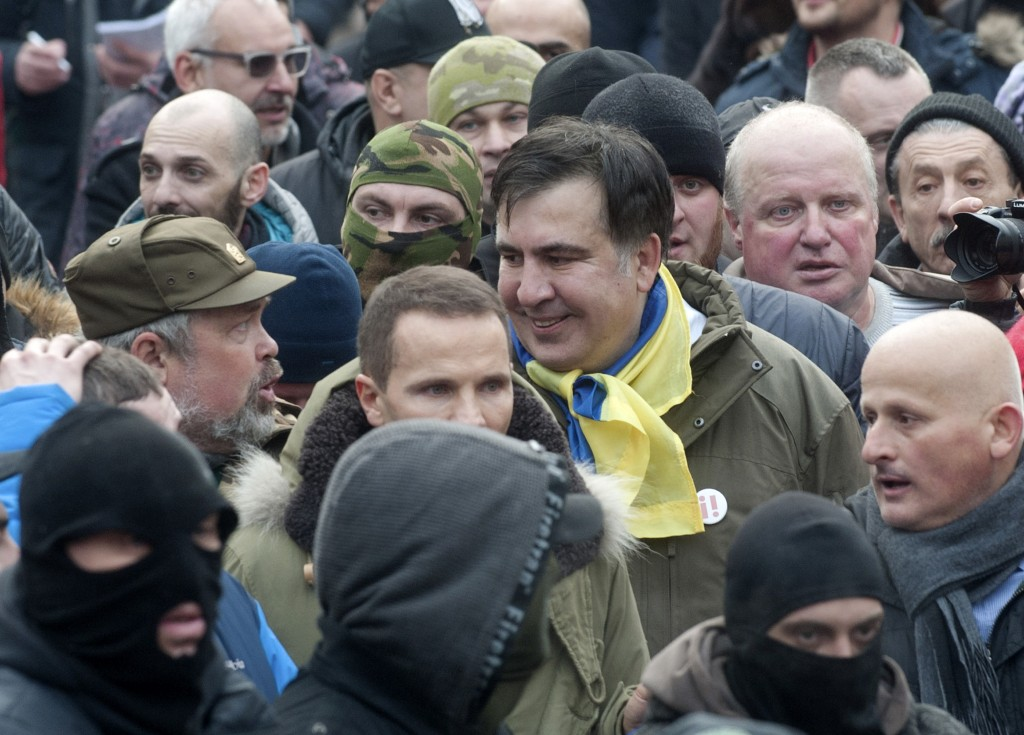 Former Georgian president Mikheil Saakashvili, center, smiles as he walks with protesters after he escaped with help from supporters and led them on a