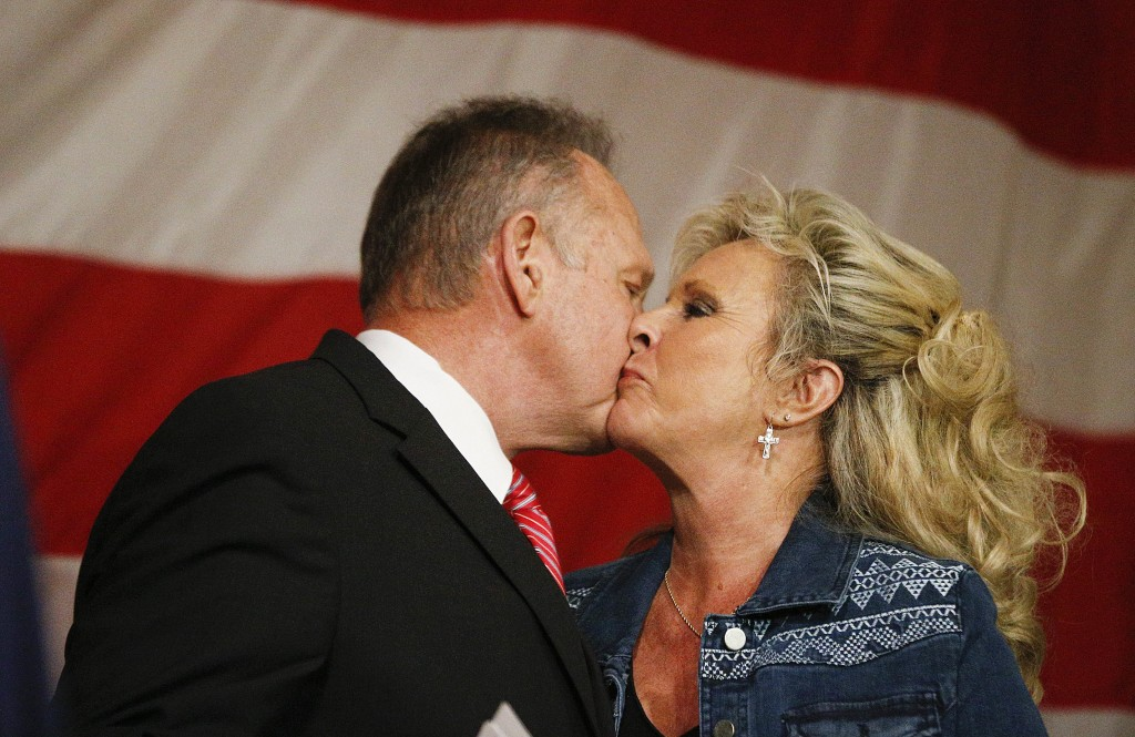 Former Alabama Chief Justice and U.S. Senate candidate Roy Moore, left, kisses his wife, Kayla Moore after he speaks at a campaign rally, Tuesday, Dec