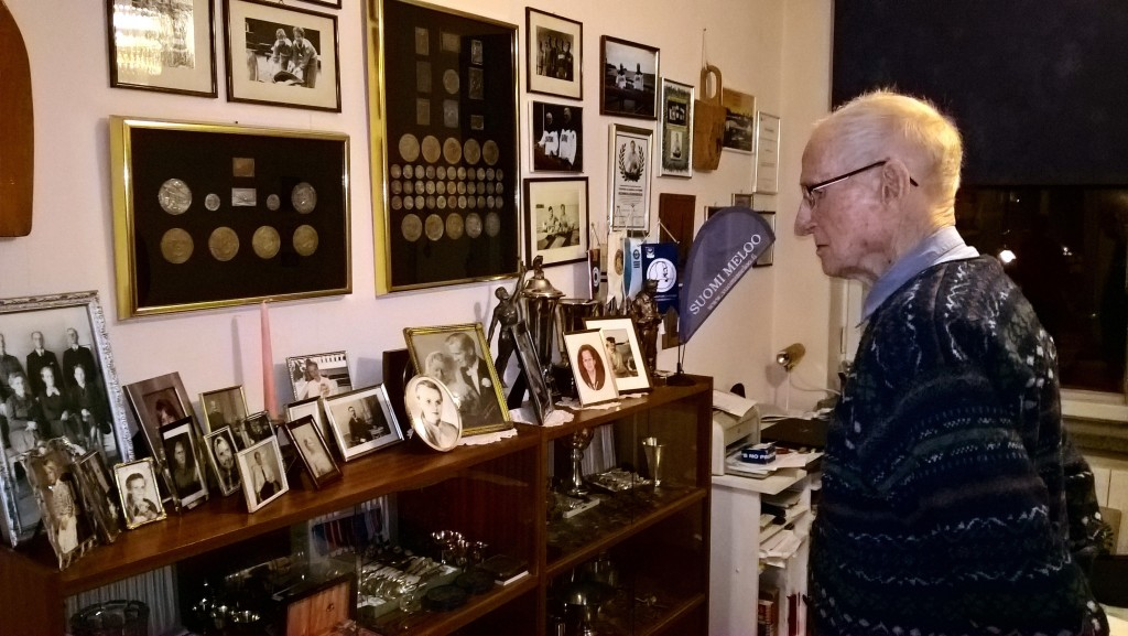 Finnish World War II veteran and Olympic athlete Torsten Liljeberg, aged 101, looks over his collection of awards and prizes received in domestic and