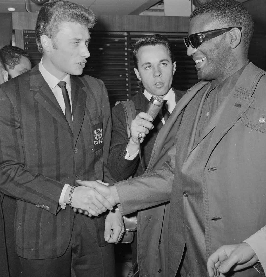 FILE- In this May 17, 1962, file photo, French singer Johnny Hallyday greets singer Ray Charles as he arrives at the Paris Orly Field in Paris. The Fr