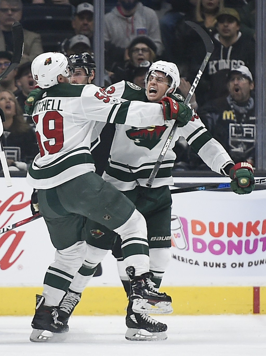 Minnesota Wild left wing Tyler Ennis, right, celebrates with right wing Zack Mitchell after Ennis scored a goal during the second period of an NHL hoc