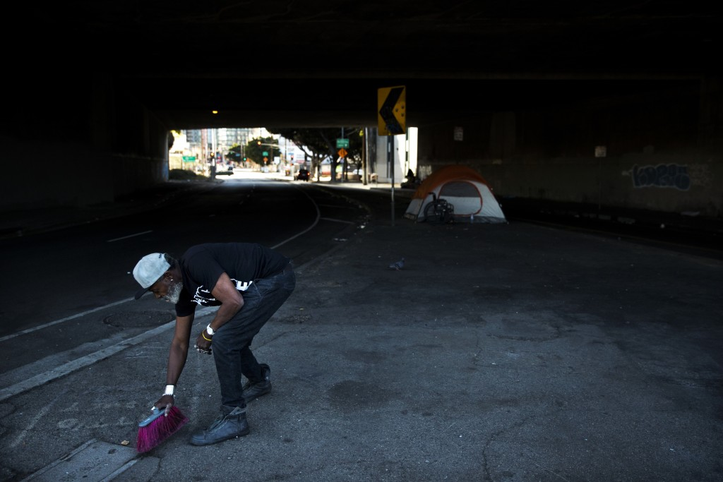 "Thurman Butler Jr., 66, who is homeless, sweeps around his tent Friday, Dec. 1, 2017, in Los Angeles. ""A lot of people in America don't realize they m"