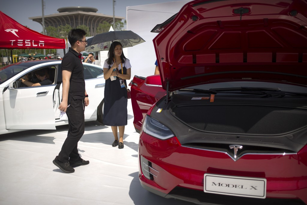 FILE - In this April 29, 2017, file photo, a visitor holds an umbrella as she looks at a Tesla Model X car on display at the G Festival, part of the G