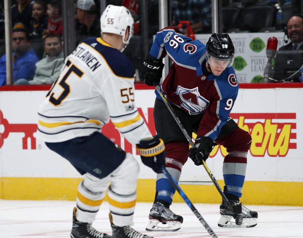 Colorado Avalanche right wing Mikko Rantanen, back, of Finland, fields a pass as Buffalo Sabres defenseman Rasmus Ristolainen, of Finland, drops back