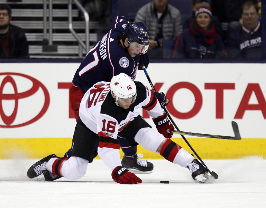 New Jersey Devils defenseman Steven Santini, bottom, gets tangled up with Columbus Blue Jackets forward Josh Anderson during the first period of an NH