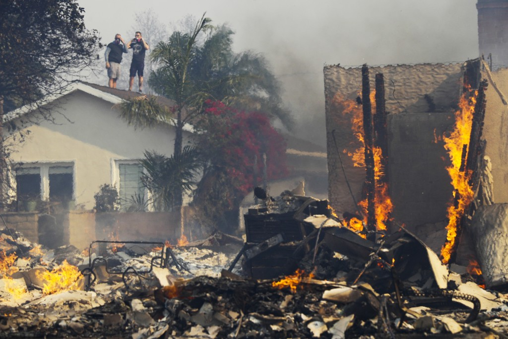 Two residents watch from a rooftop as a home burns in a wildfire Tuesday, Dec. 5, 2017, in Ventura, Calif. Raked by ferocious Santa Ana winds, explosi