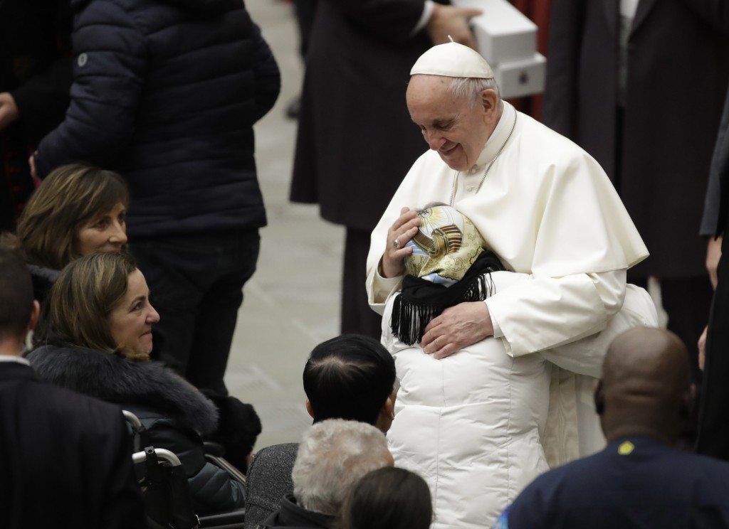 Pope Francis is hugged by a woman during his weekly general audience in the Paul VI Hall at the Vatican, Wednesday, Dec. 6, 2017. (AP Photo/Alessandra