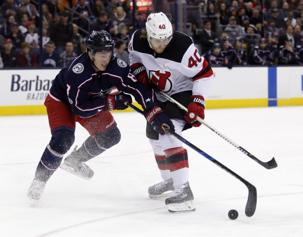 Columbus Blue Jackets defenseman Zach Werenski, left, reaches for the puck against New Jersey Devils forward Blake Coleman during the first period of