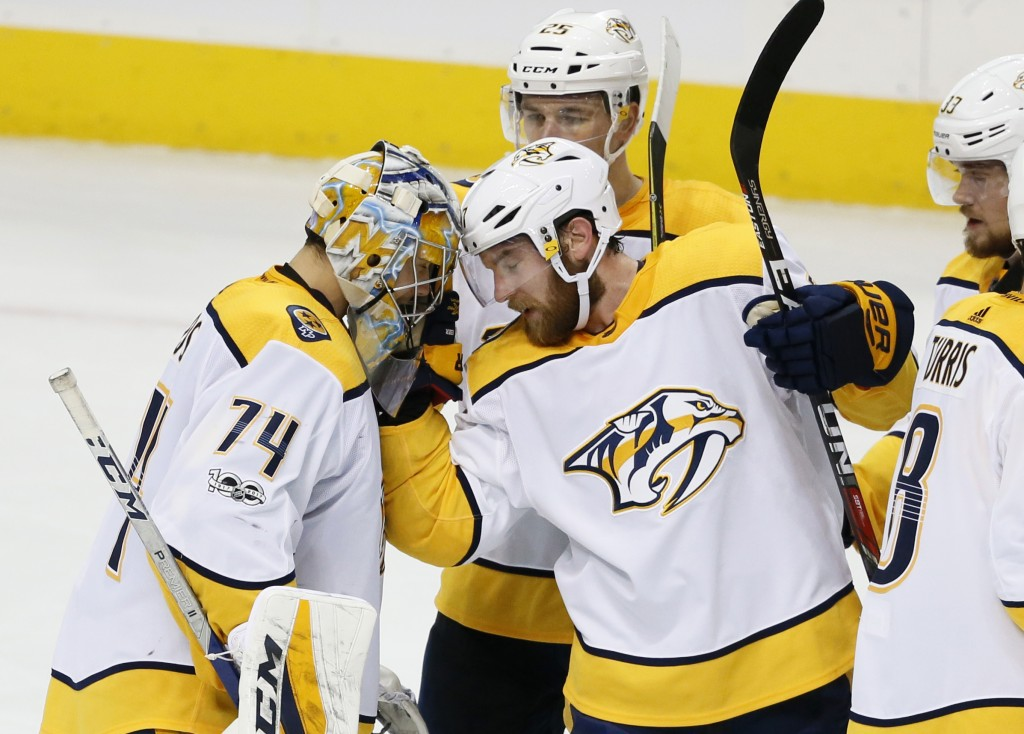 Nashville Predators goalie Juuse Saros (74) is congratulated by defenseman Yannick Weber, front center, Alexei Emelin (25) and Viktor Arvidsson after