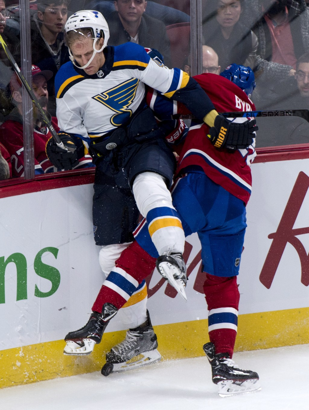 St. Louis Blues' Carl Gunnarsson, left, is checked into the boards by Montreal Canadiens' Paul Byron during the third period of an NHL hockey game, Tu