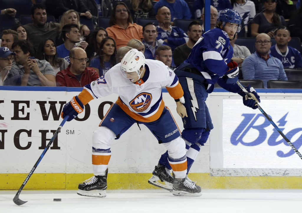 New York Islanders left wing Anders Lee (27) steals the puck from Tampa Bay Lightning defenseman Victor Hedman (77) during the first period of an NHL