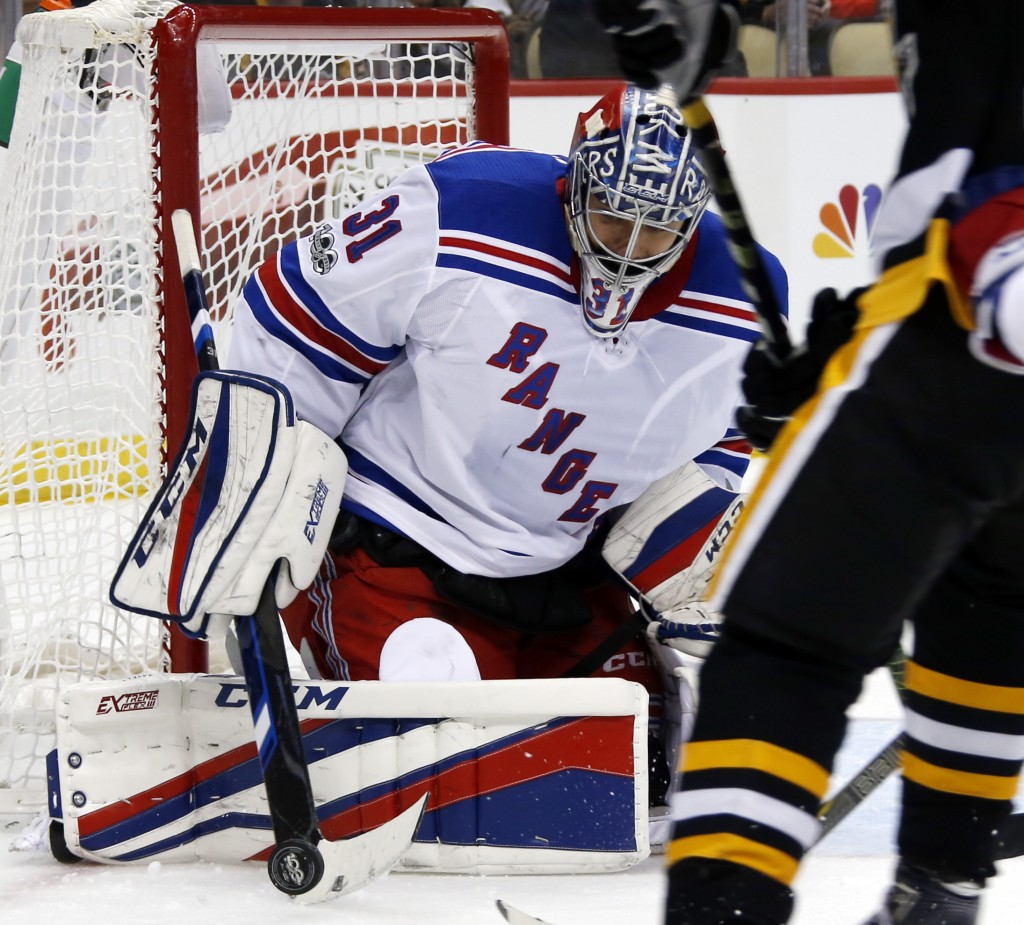 New York Rangers goalie Ondrej Pavelec (31) stops a shot by the Pittsburgh Penguins during the second period of an NHL hockey game in Pittsburgh, Tues