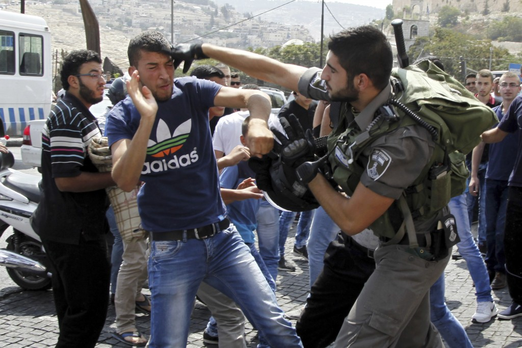 FILE - In this Friday, Oct. 2, 2015, file photo, Israeli border policeman exchanges blows with a Palestinian man during a confrontation after Friday p