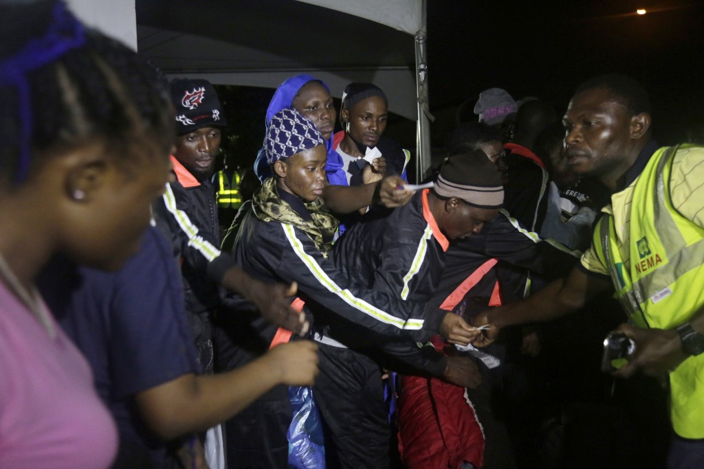 Nigerian returnees from Libya hand over their baggage tags to an official of National Emergency Management Agency after been process upon arrival at t