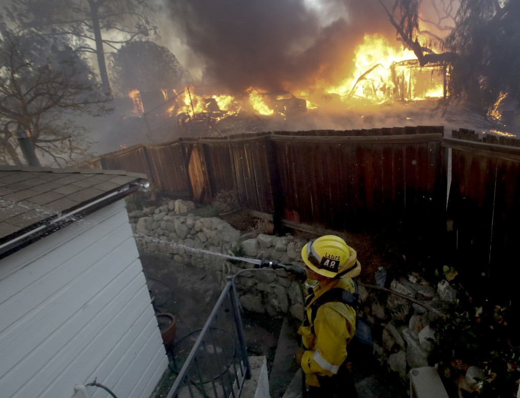 A Los Angeles County firefighter puts water on a burning roof during a wildfire in the Lake View Terrace area of Los Angeles Tuesday, Dec. 5, 2017. Fe