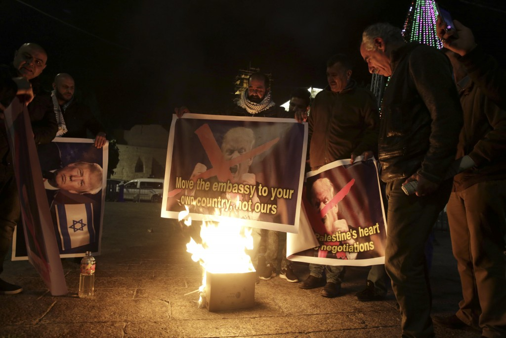 Palestinian burn a poster of the U.S. President Donald Trump during a protest in Bethlehem, West Bank, Tuesday, Dec. 6, 2017. President Trump forged a