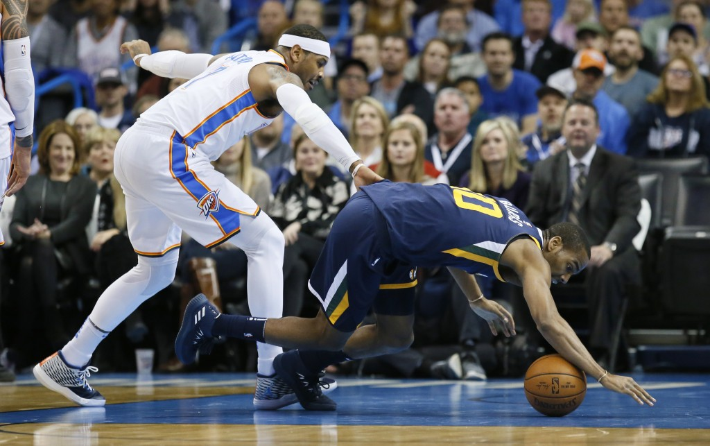 Utah Jazz guard Alec Burks (10) reaches for a loose ball in front of Oklahoma City Thunder forward Carmelo Anthony, left, in the first quarter of an N