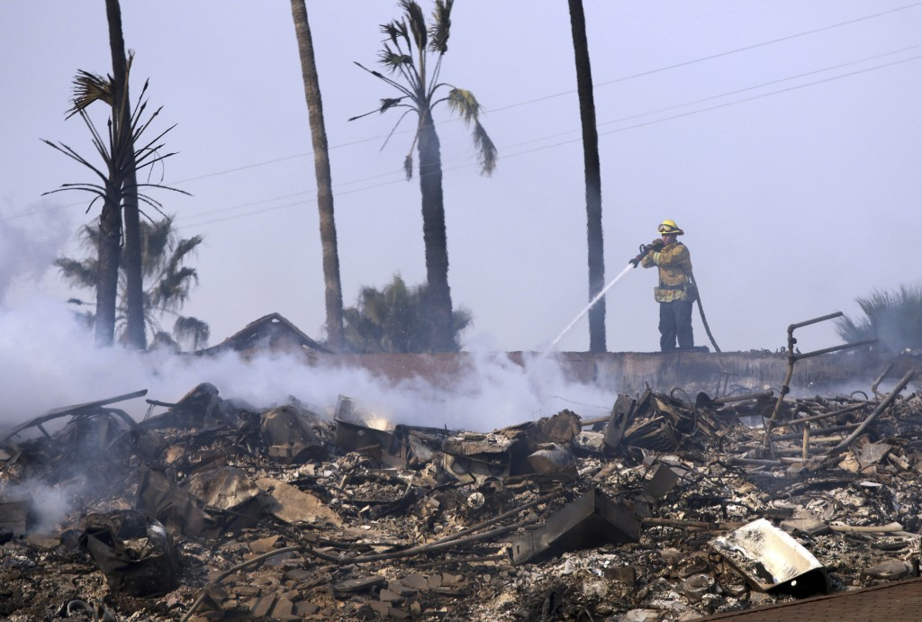A firefighter hoses down the remains of a destroyed home after the Thomas fire swept through Ventura, Calif., Tuesday, Dec. 5, 2017. (Daniel Dreifuss