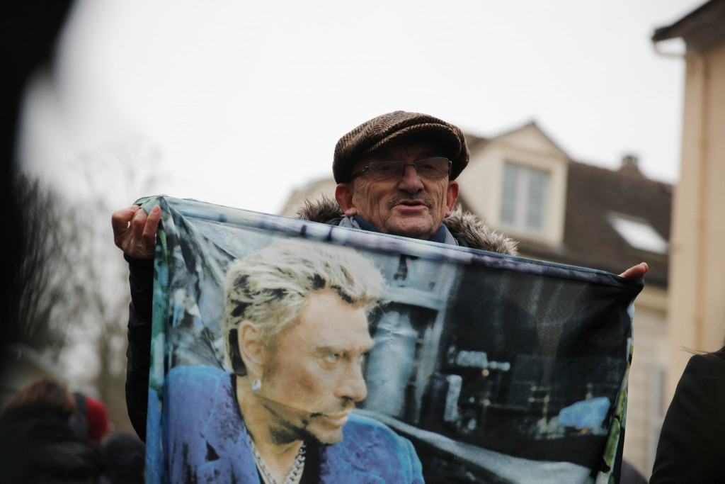 French fan Andre Duval displays a portrait of Johnny Hallyday outside his house in Marnes-la-Coquette, outside Paris, Wednesday, Dec.6, 2017. Johnny H