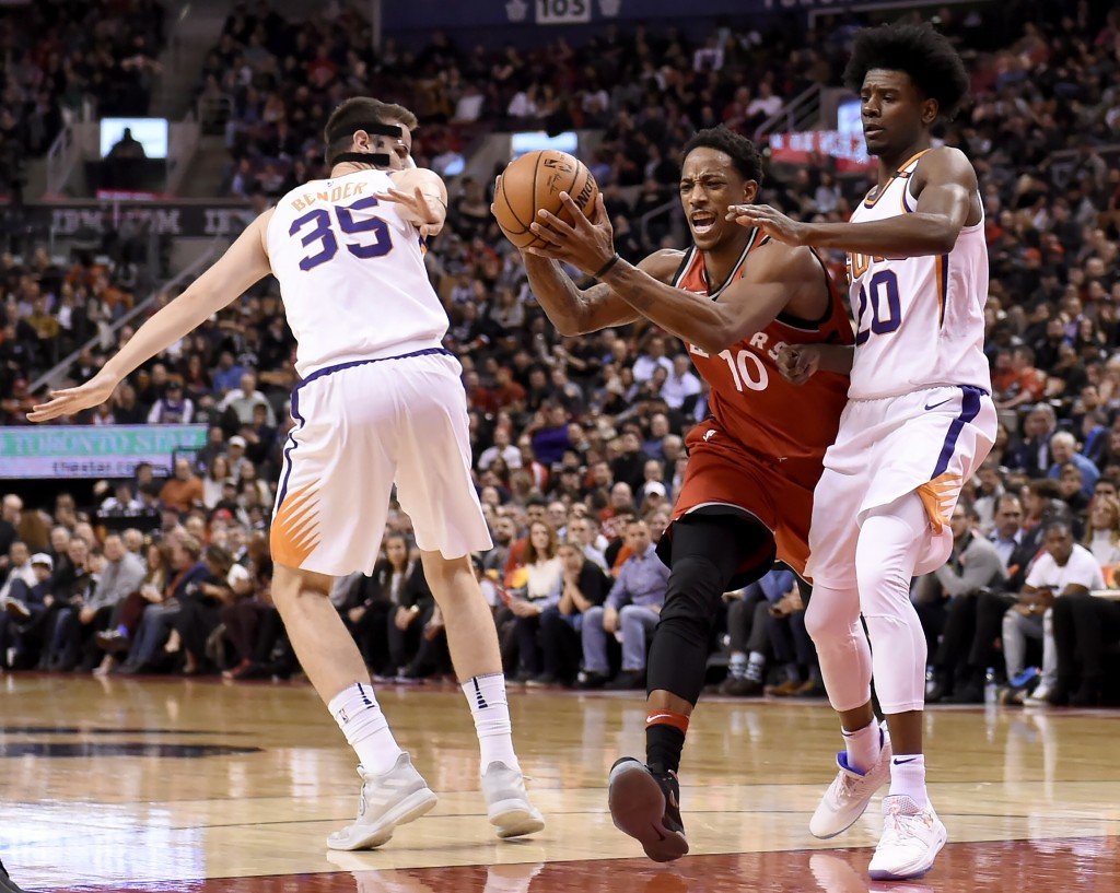 Toronto Raptors guard DeMar DeRozan (10) is fouled as he drives between Phoenix Suns' Dragan Bender (35) and Josh Jackson (20) during the second half