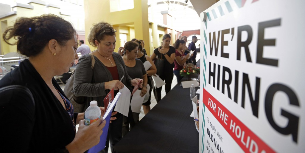 FILE - In this Tuesday, Oct. 3, 2017, file photo, job seekers wait in line to apply for part-time, full-time or seasonal positions at a job fair held