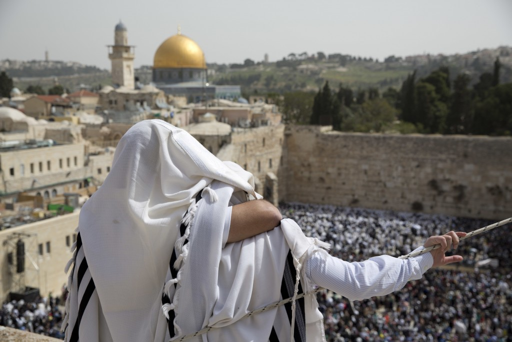 FILE - In this April 13, 2017, file photo, covered in prayer shawls Jewish men of the Cohanim priestly caste participate in a blessing during the Pass