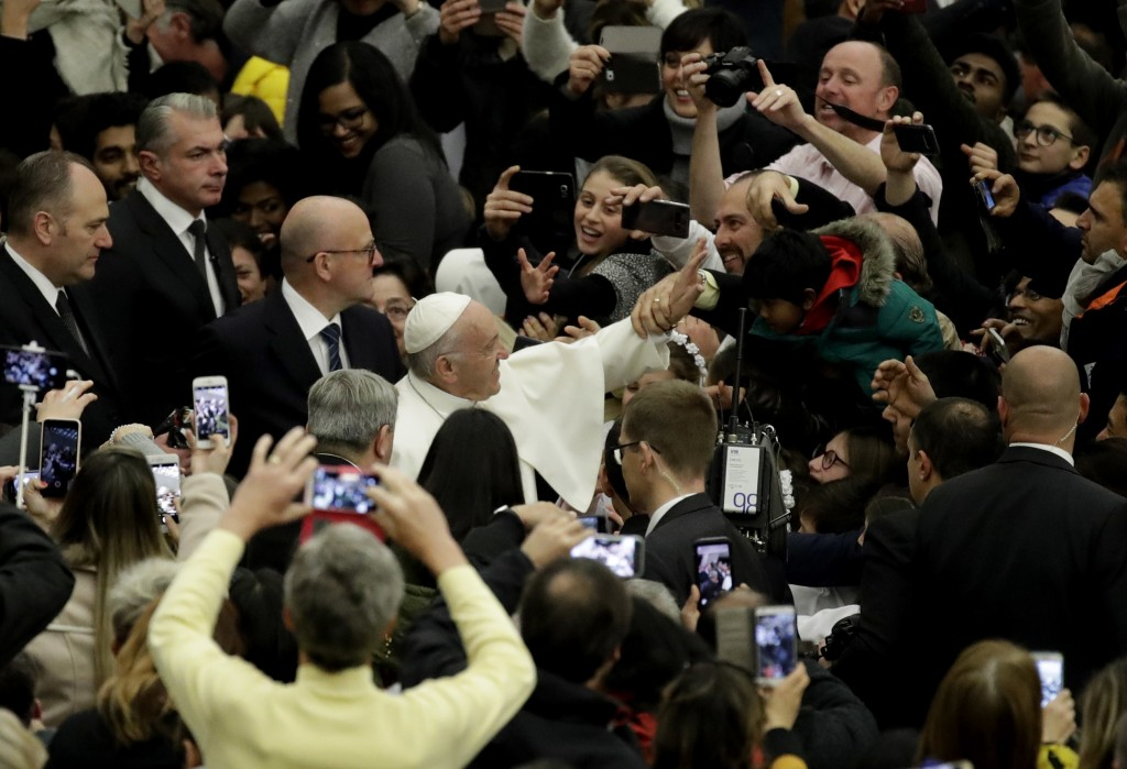 Pope Francis waves to the crowd as he arrives for his weekly general audience in the Paul VI Hall at the Vatican, Wednesday, Dec. 6, 2017. (AP Photo/A
