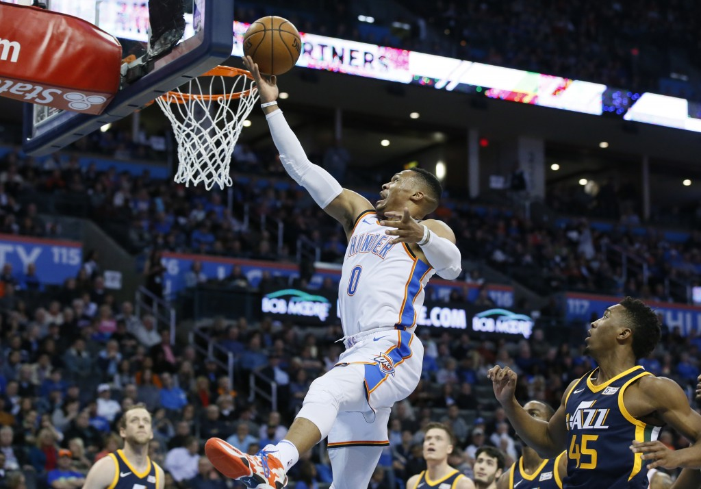 Oklahoma City Thunder guard Russell Westbrook (0) shoots in front of Utah Jazz guard Donovan Mitchell (45) in the first quarter of an NBA basketball g