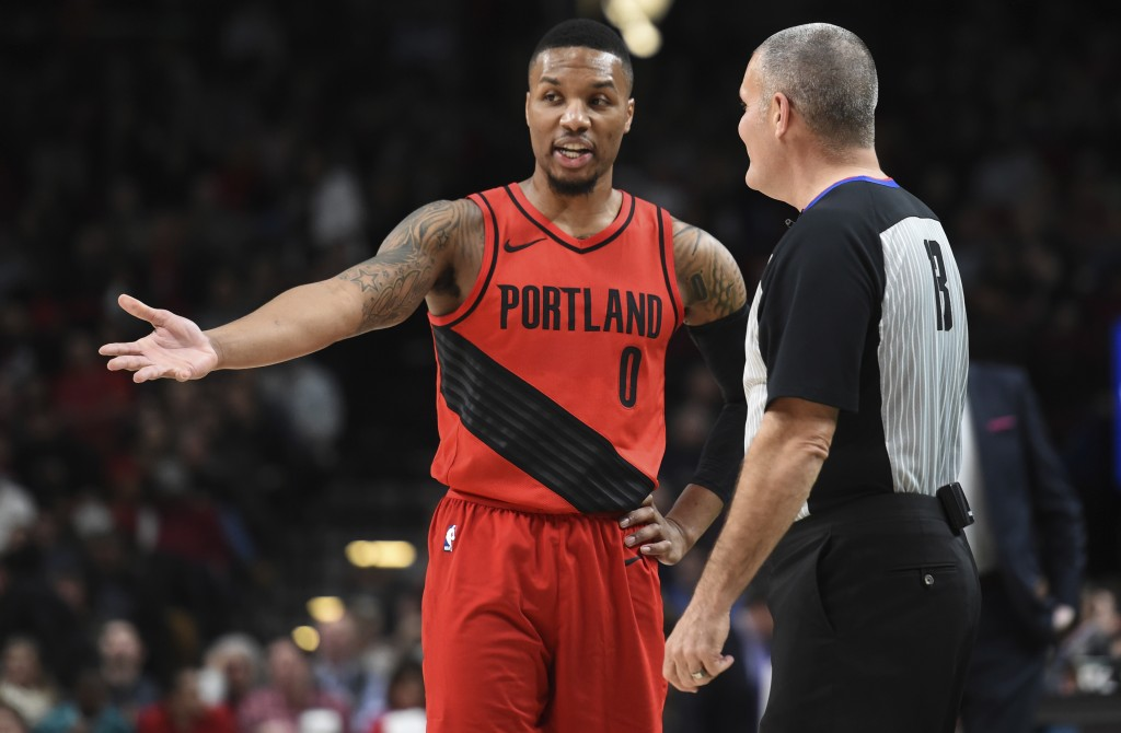 Portland Trail Blazers guard Damian Lillard has some words with referee Monty McCutchen during the first half of an NBA basketball game against the Wa
