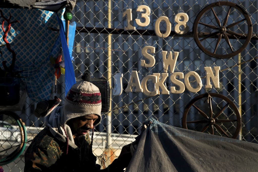 Thaddeus Bell, 50, who is homeless, sits outside his tent with the street address of his childhood home in Oklahoma hanging on a fence Monday, Dec. 4,