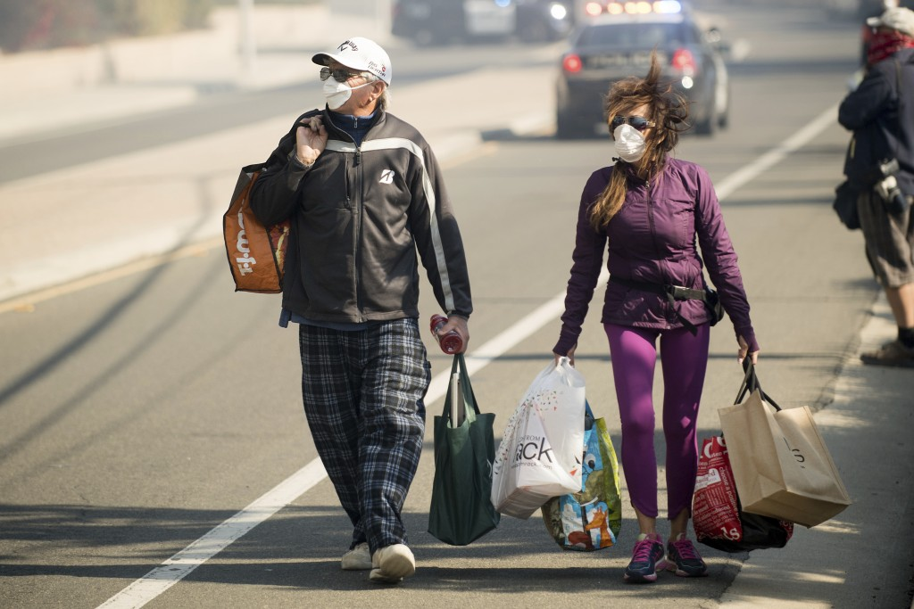 James and Josie Ralstin carry belongings from their Ventura, Calif., home on Tuesday, Dec. 5, 2017. The couple evacuated early Tuesday morning as a wi
